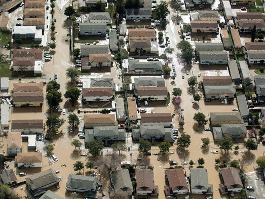 Floodwaters surround homes and cars on  in San Jose,