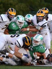 Novi's Kyle Klosterman, who rushed for 101 yards on 20 carries, is sandwiched between Hartland's Jacob Hartman on top and Tommy Lappin for a loss on the play.