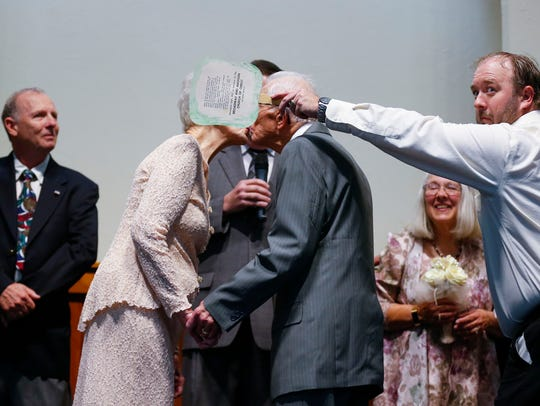 Ruth and Doyal Lindsey kiss as one of their grandchildren blocks it from view during a vow renewal ceremony for their 75th wedding anniversary at the Sunset Church of Christ on Saturday, Nov. 18, 2017.