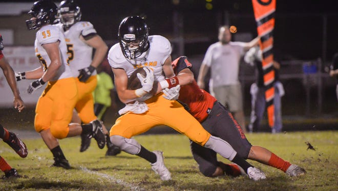 Merritt Island High quarterback Mason Denaburg is brought down by Satellite High's Andrew Abendroth during the first half of Friday's game.
