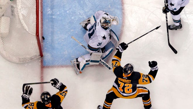 The overtime goal by Pittsburgh Penguins' Conor Sheary, not seen, bounces out of the net behind San Jose Sharks goalie Martin Jones (31) with Marc-Edouard Vlasic (44) defending as Penguins' Sidney Crosby (87) and Patric Hornqvist (72) begin to celebrate Wednesday in Game 2 of the Stanley Cup Final series. The Penguins won 2-1.