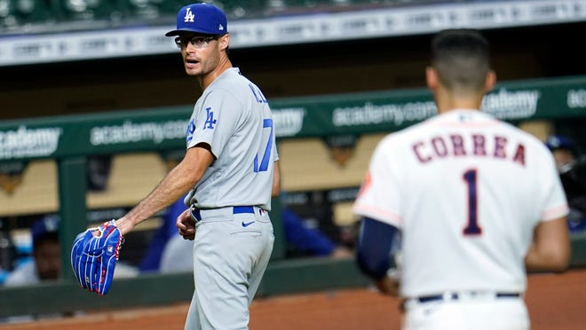 Los Angeles Dodgers relief pitcher Joe Kelly (17) looks back at Houston Astros' Carlos Correa (1) after the sixth inning of a baseball game Tuesday, July 28, 2020, in Houston. Both benches emptied during the exchange.