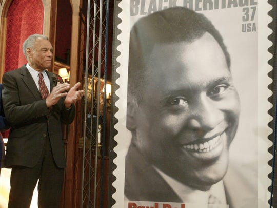 Paul Robeson Jr. applauds in 2004 after the unveiling of a U.S. postage stamp during a ceremony honoring his father and the new stamp at Kirkpatrick Chapel at Rutgers University, where Robeson attended college and played football.