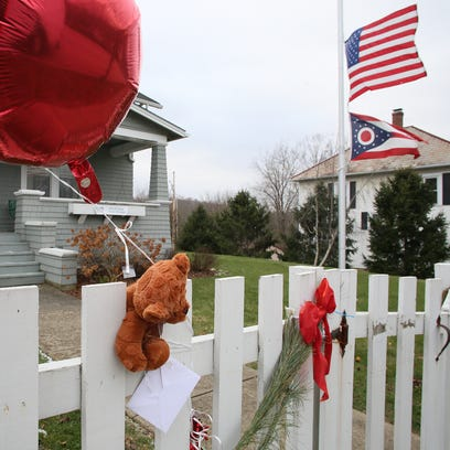 A teddy bear, balloons and flowers hang on the fence