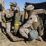 Marine artillerymen assigned to Task Force Spartan, 26th Marine Expeditionary Unit, prepare an Excalibur 155 mm round aboard Fire Base Bell in Iraq on March 18. The Marines are conducting fire missions against the Islamic State group.