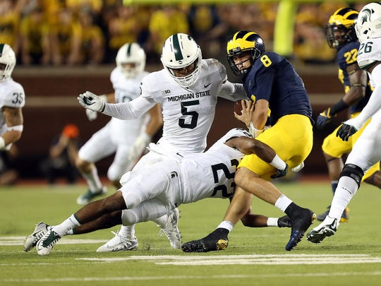 Michigan QB John O'Korn (8) is sacked by Michigan State