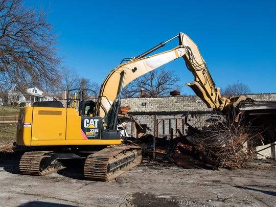 A bulldozer from DP Schweihofer Excavating, Inc., demolishes