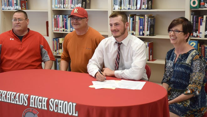Riverheads' Ridge Stokes signs his letter of intent to play football at West Virginia Wesleyan College in the high school library on Wednesday, April 12, 2017, in Greenville. From right are his mother Stephanie, his father Mike and Gladiators head football coach Robert Casto.