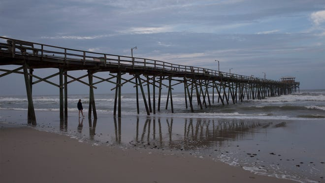 A beachcomber walks by the Oceanana Fishing Pier in Atlantic Beach, N.C. Hurricane Arthur began moving offshore and away from North Carolina's Outer Banks early Friday after hitting the state's barrier islands overnight and causing flooding and thousands of power outages.