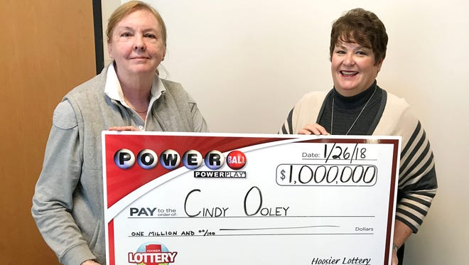 Cindy Ooley of Fishers holds the ceremonial check for $1 million Powerball win with Hoosier Lottery Executive Director Sarah Taylor.