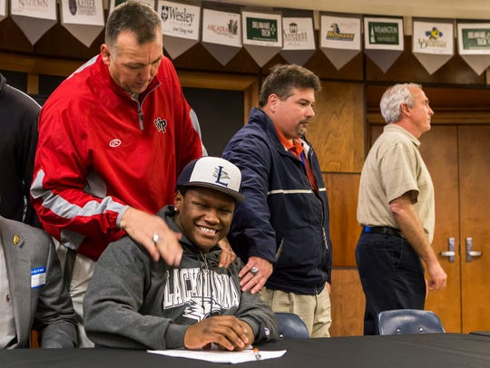 William Penn football coach Marvin Dooley congratulates Titus Nelson after the fullback signed with Lackawanna Community College in 2016.