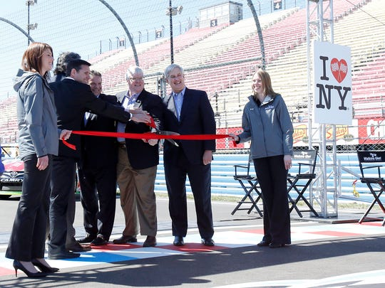 Watkins Glen International officials and government officials cut the ribbon at the unveiling of the newly resurfaced racetrack Friday at the road course.