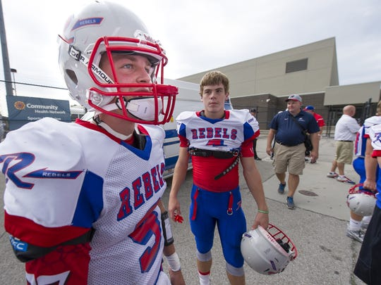 Roncalli High School senior Robbie Strader (9) talks with teammates during pre-game activities of a high school varsity football game at Lawrence Central High School, Friday, September 4, 2015, in Indianapolis.