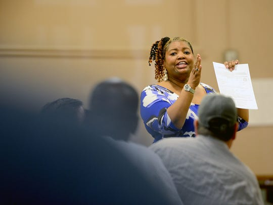 Sualyn Holbrook, Ingham County Department of Health and Human Services director, goes over the application for State of Emergency relief with residents of the Homeless Hotel Thursday, Sept. 1, 2016, at Cristo Rey Catholic Church in Lansing.