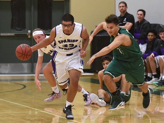 Spanish Springs' Marcus Loadholt run away with a loose ball with Saint Marys' Joe Long chasing him in the first half of Thursday's game at the Wild West Shootout at Bishop Manogue.