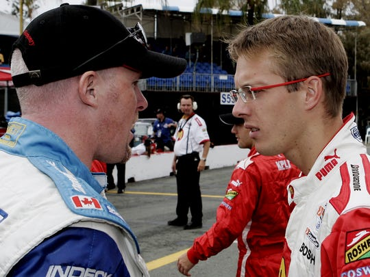France's Sebastien Bourdais, right, chats with Canadian driver Paul Tracy in pit lane prior to the first practice session for the Indy 300 at the Surfers Paradise street circuit on the Gold Coast Australia, Friday, Oct 21, 2005.