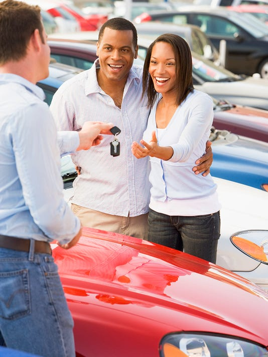 Couple picking up new car from salesman