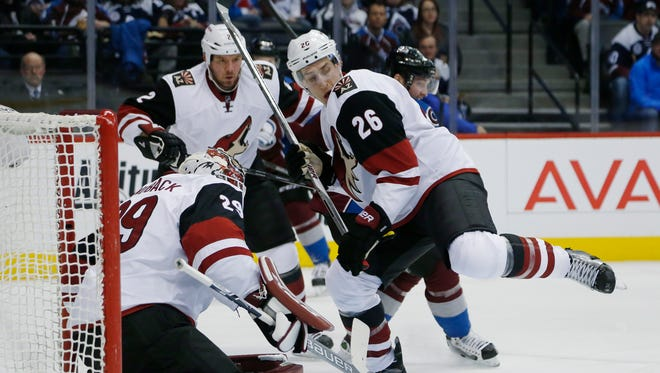 Arizona Coyotes goalie Anders Lindback (29), front, left, of Sweden, stops shot as defenseman Michael Stone, front right, pursues the puck while checking Colorado Avalanche center Matt Duchene, back, right, in the first period of an NHL hockey game Sunday, Dec. 27, 2015, in Denver.