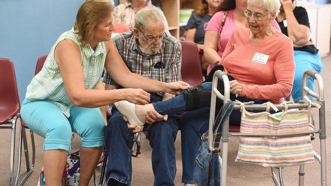 Bonnie Dozier, left, adjusts a leg braces for her mother-in-law, C.C. Dozier at a Weight Watchers meeting on Tuesday, August 23, 2016.