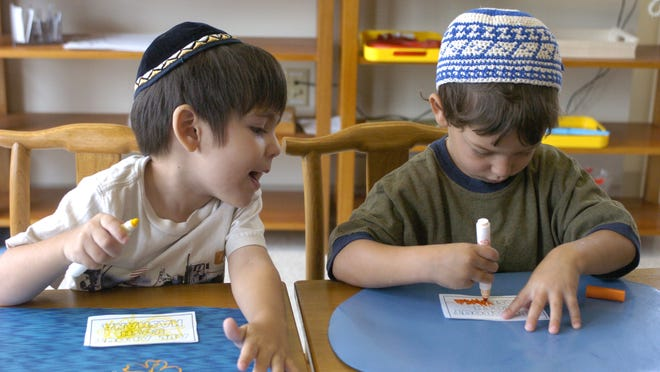 David Chriqui, left, and Aidan Samuelson work on the covers of their Rosh Hashana books at the Chai Tots Montessori Preschool at the Jewish Discovery Center in Mason.