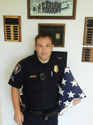 In this photo provided Monday, July 4, 2016, by the Willard Police Department, Cpl. Steve Purdy poses for a photo in Willard, Mo., with a folded U.S. flag the police located after it went missing in an upstate New York campground. The flag that had draped the casket of Cathy Scoppo's World War II veteran father had gone missing while on display at the upstate New York campground she manages. But on Monday, the nation's 240th birthday, the flag was headed her way, days after police 1,700 miles away in southwestern Missouri got it back from a teenager they suspect pilfered it while visiting the campsite. (Willard Police Department via AP)