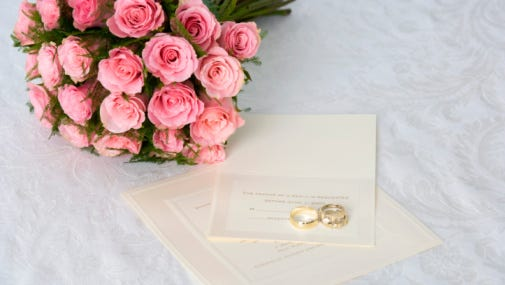 Wedding bouquet of pink roses and wedding rings on invitation.