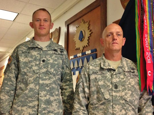 "In a hallway filled with history, Lt. Col. Ryan Wylie and Command Sgt. Maj. Matthew Bartel stand proudly with the newly unfurled colors of the 1st Battalion, 26th Infantry Regiment ""Blue Spaders,"" now part of the 101st Airborne Division (Air Assault)."