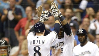 Ryan Braun and Jonathan Villar celebrate after scoring on a two-run triple hit by Hernan Perez during the seventh inning against the Rockies on Tuesday.