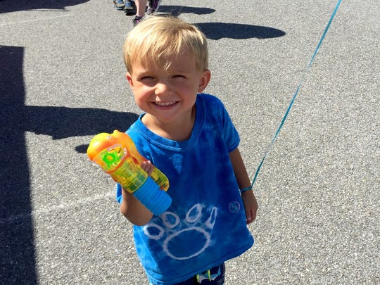 Sean DeVries, 3, of Waynesboro grins after his mother bought him a light up bubble gun.