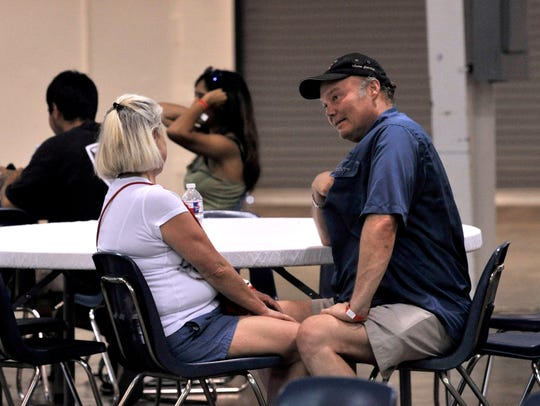 Pete Sugg of San Antonio fans himself with his shirt as he and Stephanie Oxford cool off inside the Round Building at the Taylor County Expo Center.