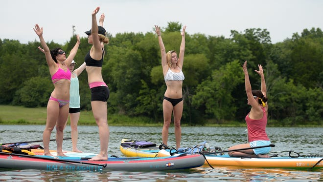 Nashville Paddle Co. yoga instructor Sara Bradley, left, teaches a yoga standup paddleboarding class at Percy Priest Lake.