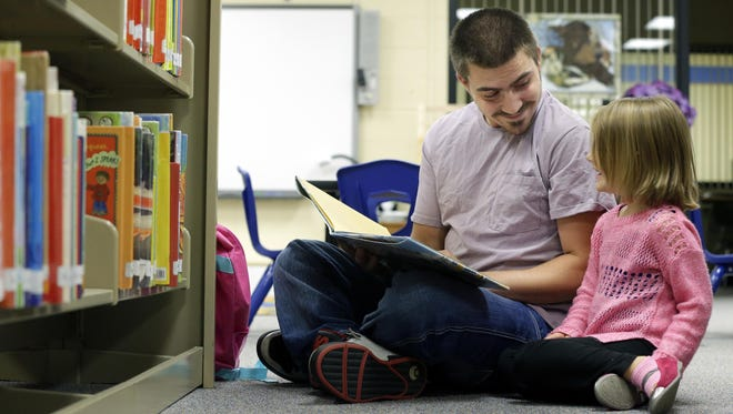 Coty Brouchoud reads a book to his daughter Theia, 4, during an open house Tuesday at the Washington Early Learning Center in Neenah.
