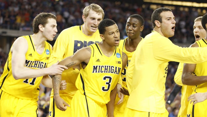 Michigan star Trey Burke is surrounded by his teammates after he tied the game against  Kansas in Arlington, Texas, on March 29, 2013.