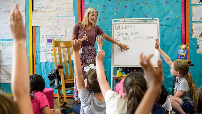 """Alexandria Craig (top), a third-grade teacher at Daniel Wertz Elementary School, asks her class how to change the sentence """"Saturday is the best day of the week"""" into a fact during a class lesson, Thursday, May 3, 2018."""