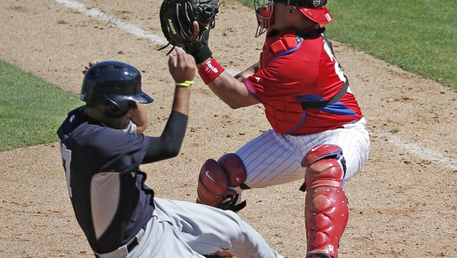 Yankees pinch runner Francisco Arcia slides into home plate as Philadelphia Phillies catcher Carlos Ruiz waits for the throw  in an exhibition game in Clearwater, Fla., on Thursday. Ruiz tagged Arcia out at the plate.