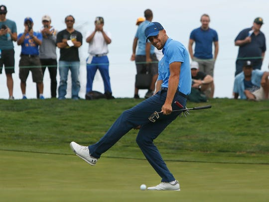 Stephen Curry tries to coax a putt into the cup on the eighth hole during the first round.