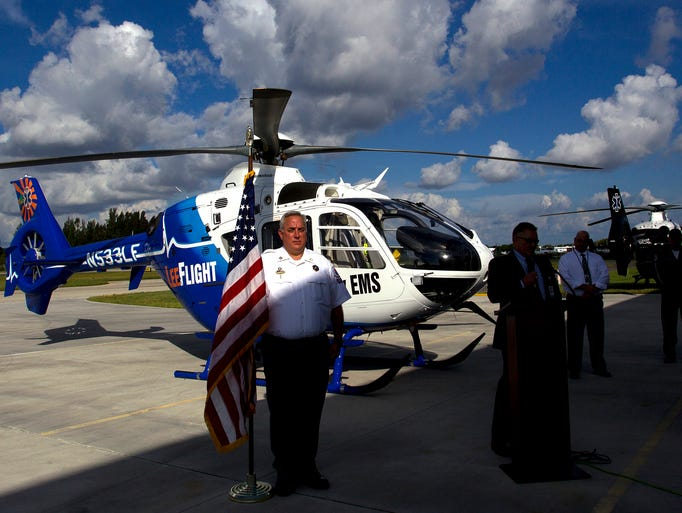 Lee County Emergency Medical Services Captain Douglas Higgins sees that Old Glory doesn't blow over during a ribbon-cutting ceremony for LeeFlight's new Eurocopter EC 135, held near the LeeFlight hangar at Page Field Airport Thursday, August 14. The event marks the LCEMS one-year anniversary with air medical transport company, Air Methods.