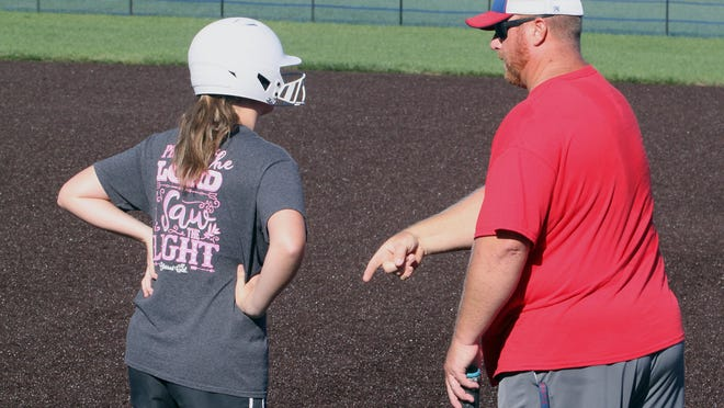 Moberly varsity softball coach Ryan Taylor points as he explains base running techniques to incoming sophomore Paige Hull during a summer workout session held July 28 at the school's General Omar Bradley Field.