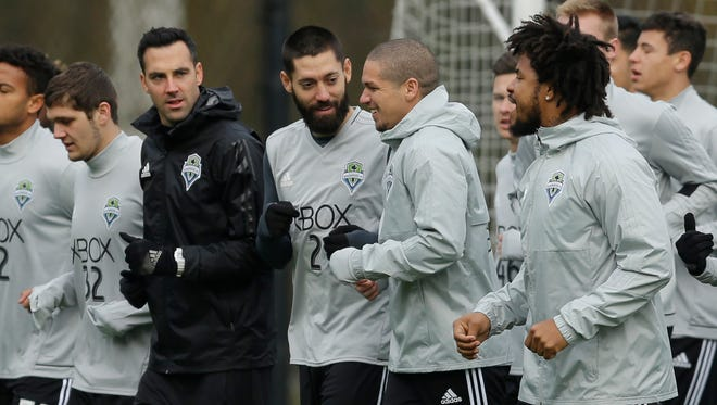 Seattle Sounders forward Clint Dempsey (center, with beard) chats with captain Osvaldo Alonso during a team jog in the first training session for the 2017 MLS season Tuesday in Tukwila.