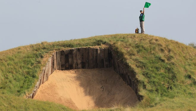 A marshall signals on the top of a bunker on the fourth fairway ahead of the 140th British Open Golf championship at Royal St George's in Sandwich, Kent, south east England.