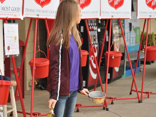 Hannah Mobley, 12, rings bells for the Salvation Army outside of Kmart in Pineville on Black Friday.