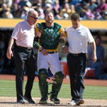 Athletics trainers assist catcher Stephen Vogt off