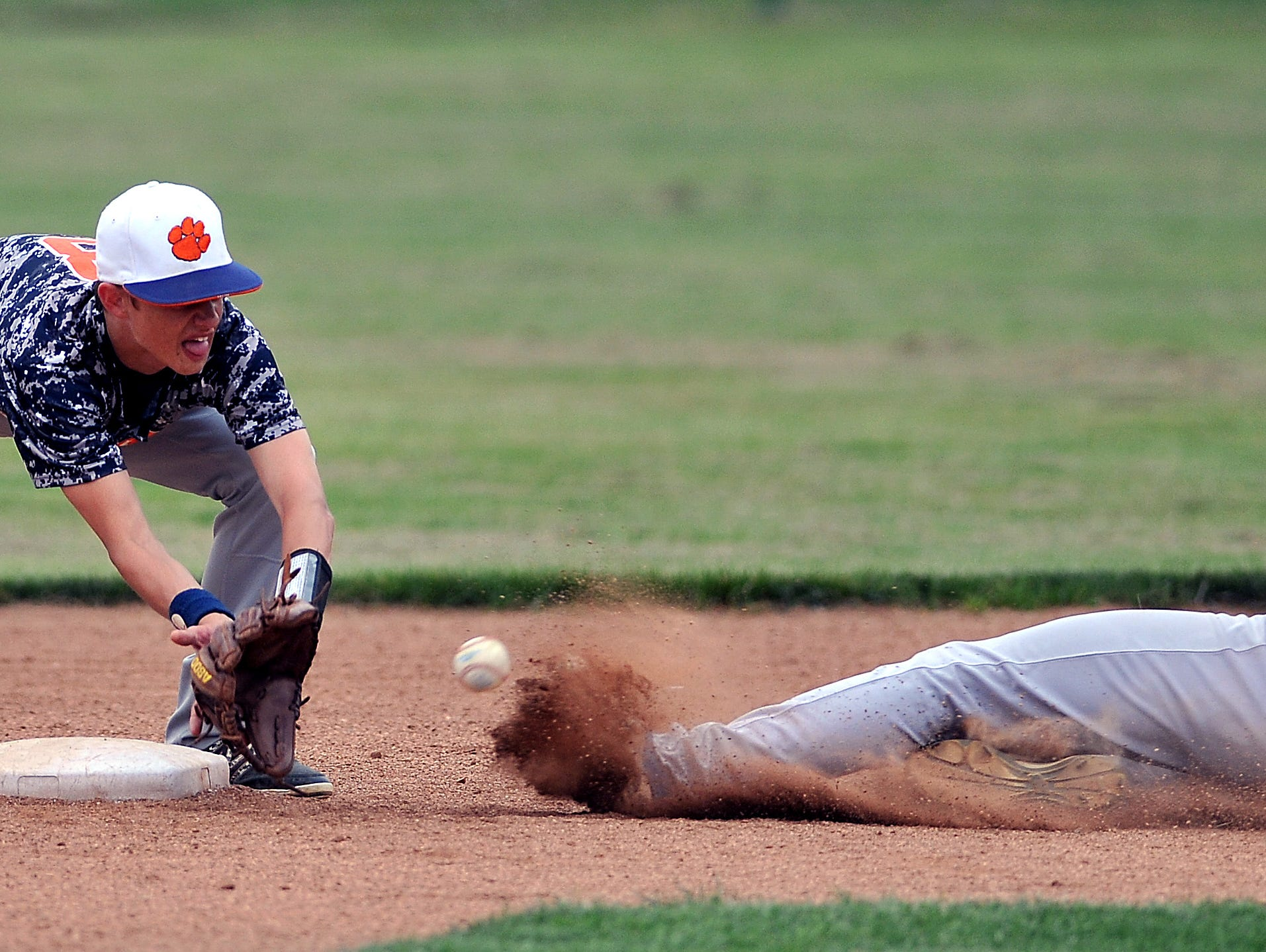 Ontario's Alex Vredenburgh slides safely into second just before the tag by Galion's Chad Karnes during the Division II sectional title baseball game at Ontario Thursday.
