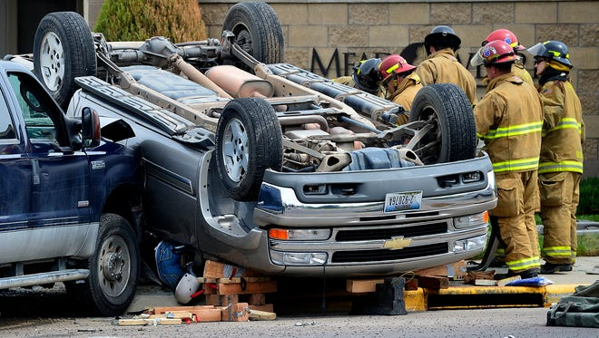 Great Falls Fire/Rescue work on extricating the driver of an overturned SUV after a two vehicle accident at the intersection of Fox Farm and Park Garden on Thursday afternoon. Three patients, one adult and two children, were taken to Benefis for treatment.