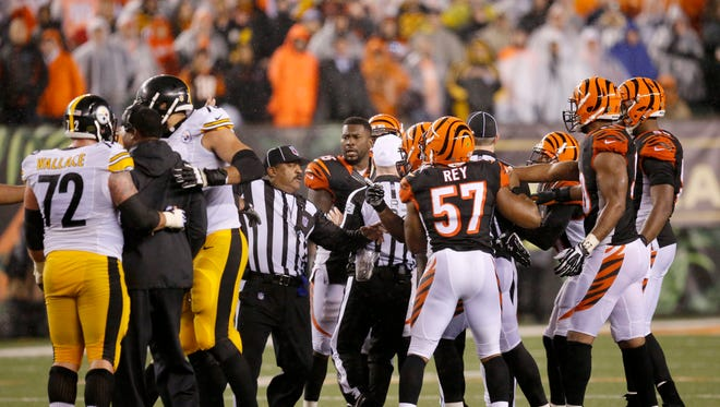 A flag flies as Bengals cornerback Adam Jones is penalized for shoving Steelers linebackers coach Joey Porter.