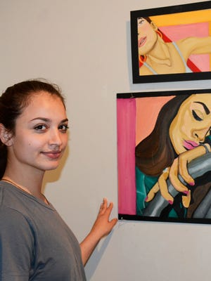 Nicole Hebert poses with some of her paintings from the Sophomore Art Show at JCJC.