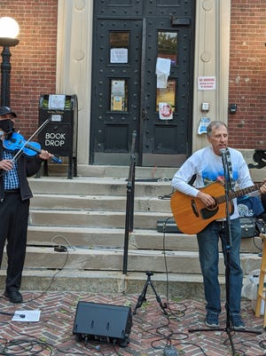 Knock on Woods - Joe Kessler on violin and Howie Newman, singer , guitarist and harmonica player - performed Monday night in front of the Bigelow Free Public Library, in Clinton.