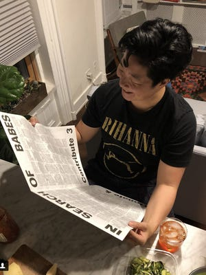 JJ Chinois looks over the newspaper Kelly Rakowski made for her Personals app launch party June 13. The newspaper was filled with personal ads from New York City LGBTQ women.