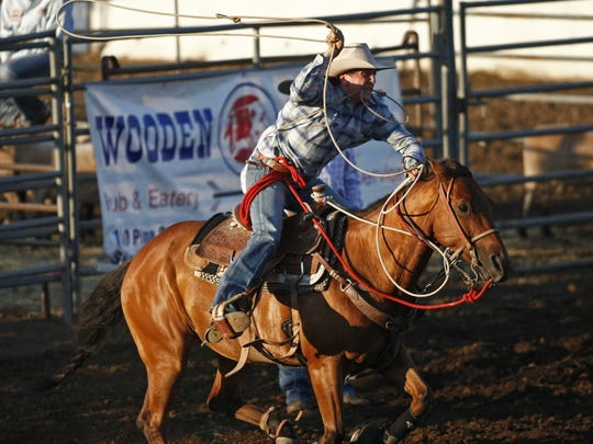 Jared Sharp and his horse charge out of the gate during the calf roping competition during the Santiam Canyon Stampede.