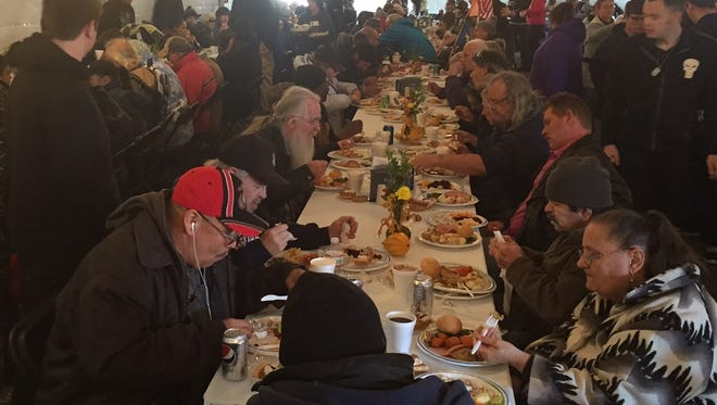 Hundreds of people sit down Tuesday to a Thanksgiving dinner in a tent at Center and Sixth streets.